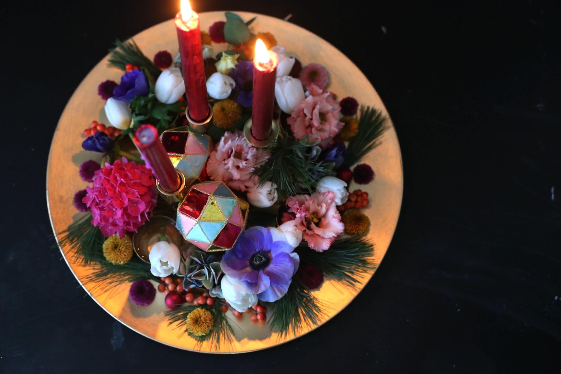 Värikäs jouluasetelma on koottu matalalle kullanväriselle lautaselle. Leikkokukkien joukossa on kolme kynttilää.