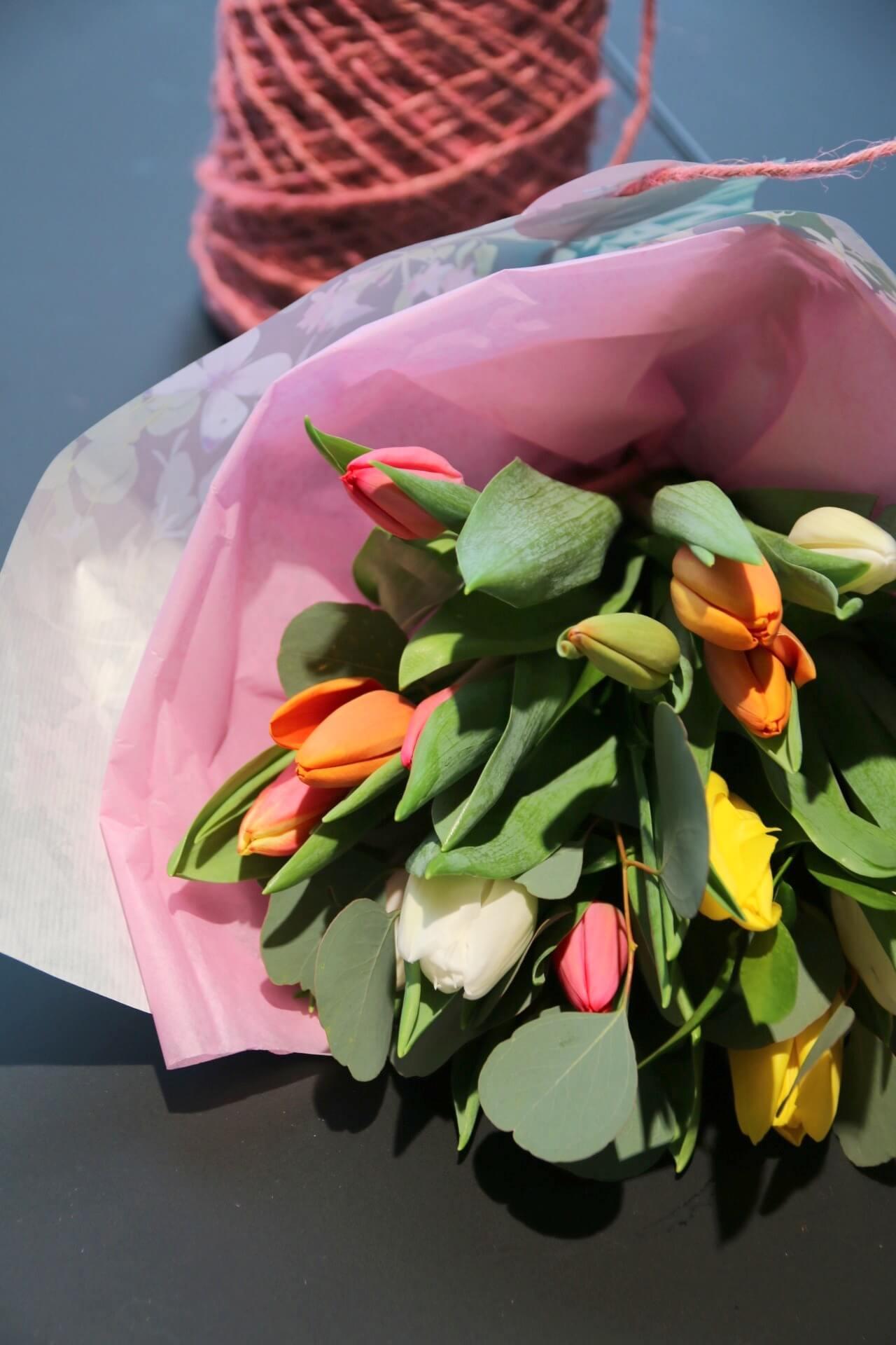 värikkäät tulppaanit on sidottu kimpuksi ja kääritty silkkipaperiin sekä sidottu juuttinarulla.