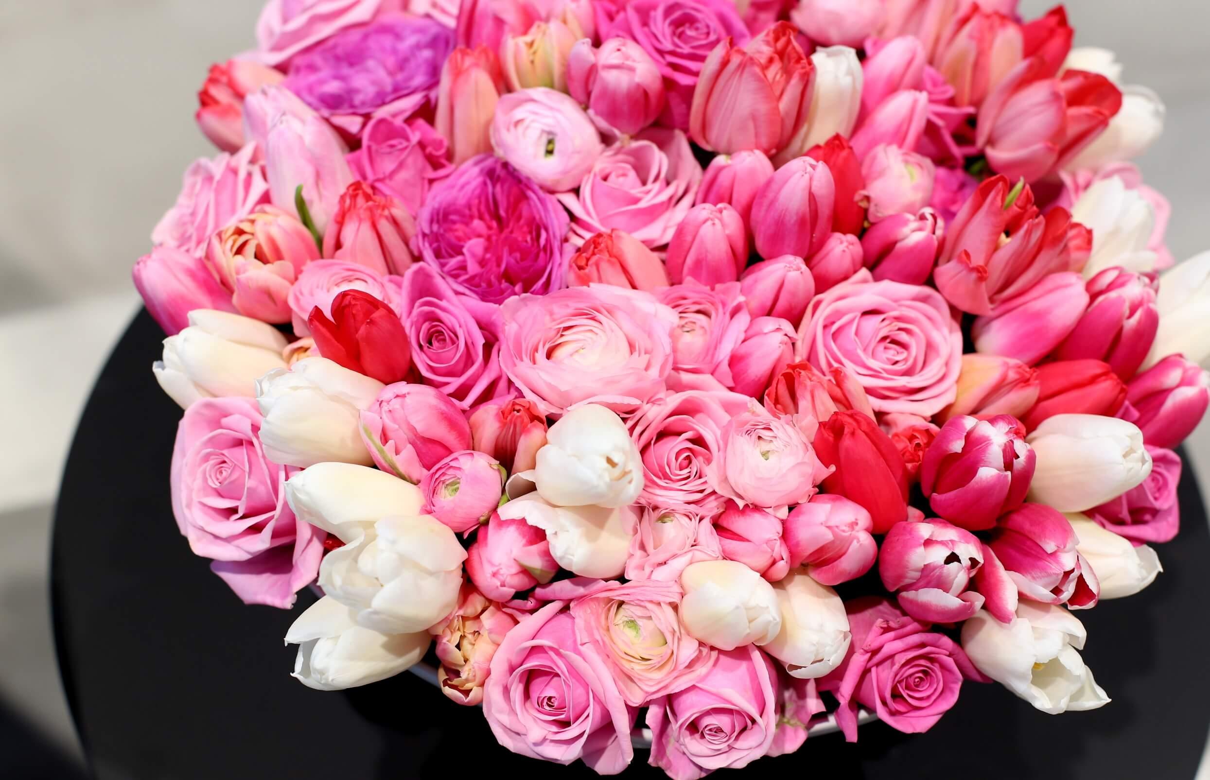 Pinkit tulppaanit ovat yhdessä ruusujen ja leinikkien kanssa matalassa asetelmassa.