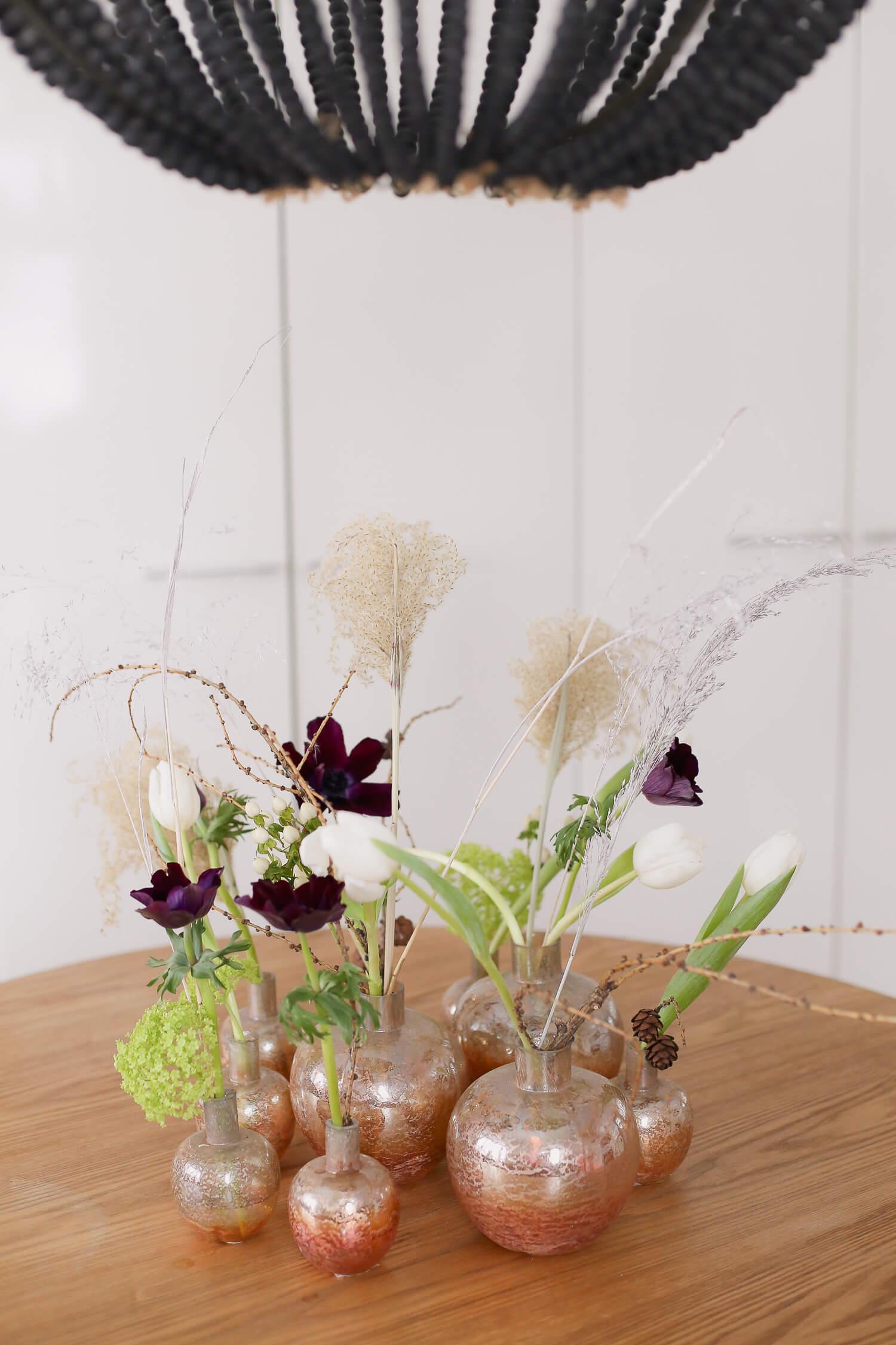 Pöydälle on koottu erilaisia maljakoita kukkakimpulle.