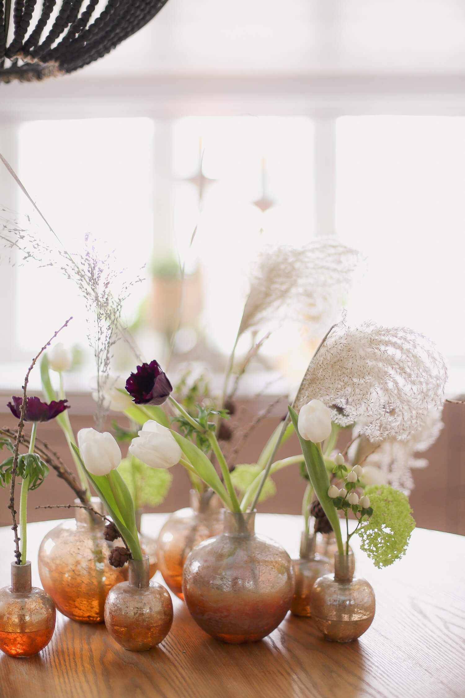 Pöydälle on koottu erilaisia maljakoita kukkakimpulle