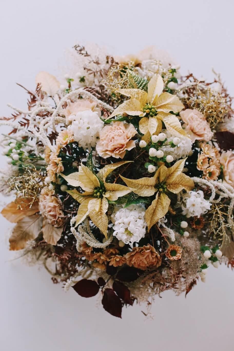 Kimpussa on valkoisia minijoulutähtiä, persikan värisiä neilikoita, krysanteemia ja kullan väristä hopealankaa. Kimppu kuin kultaa ja valoa, joulun kukkatrendien mukaan.