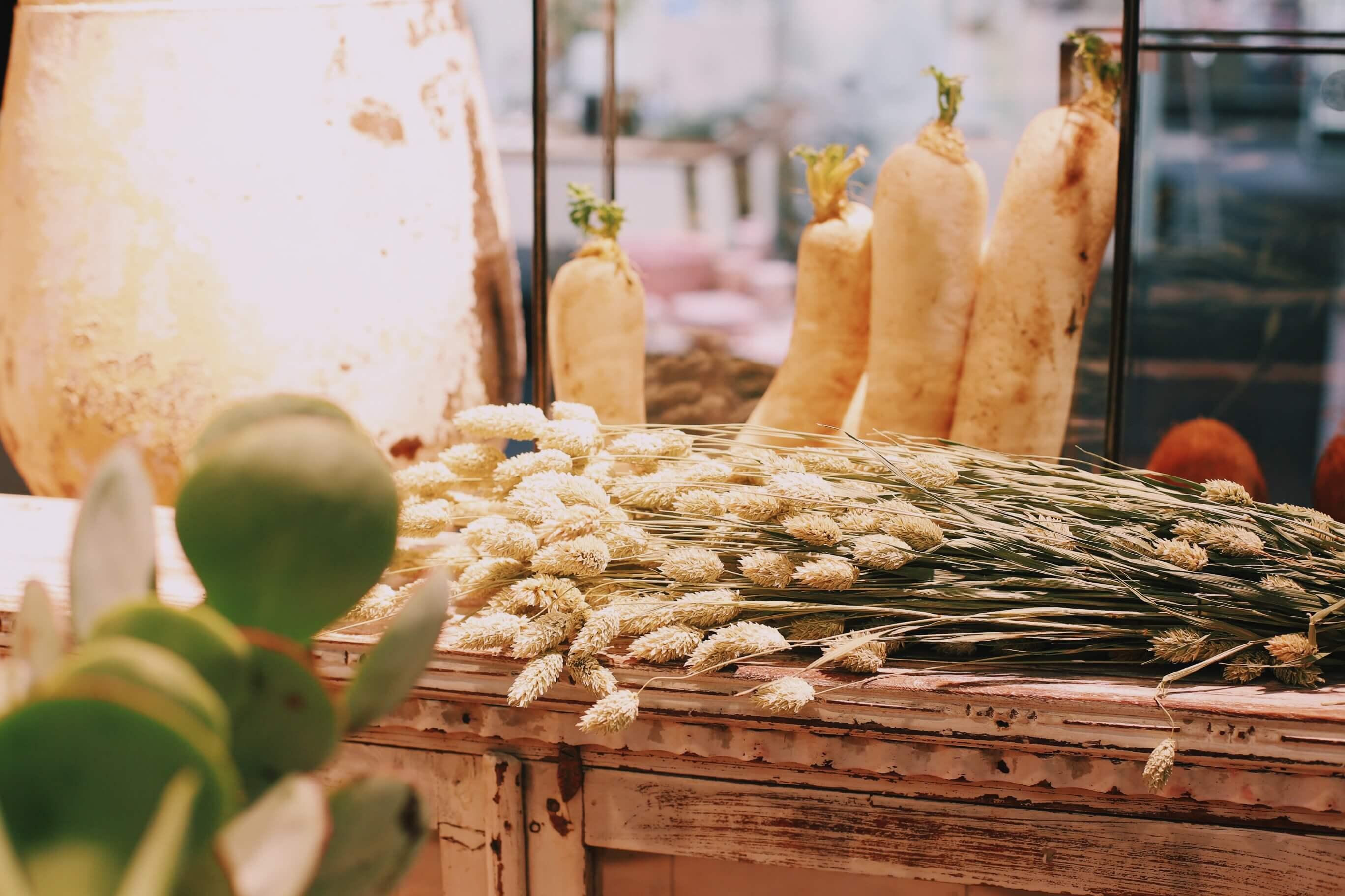 Heinänippu rennosti lipaston päällä ja taustalla palsternakat, jotka tekevät versoa, tuovat kontrastia.