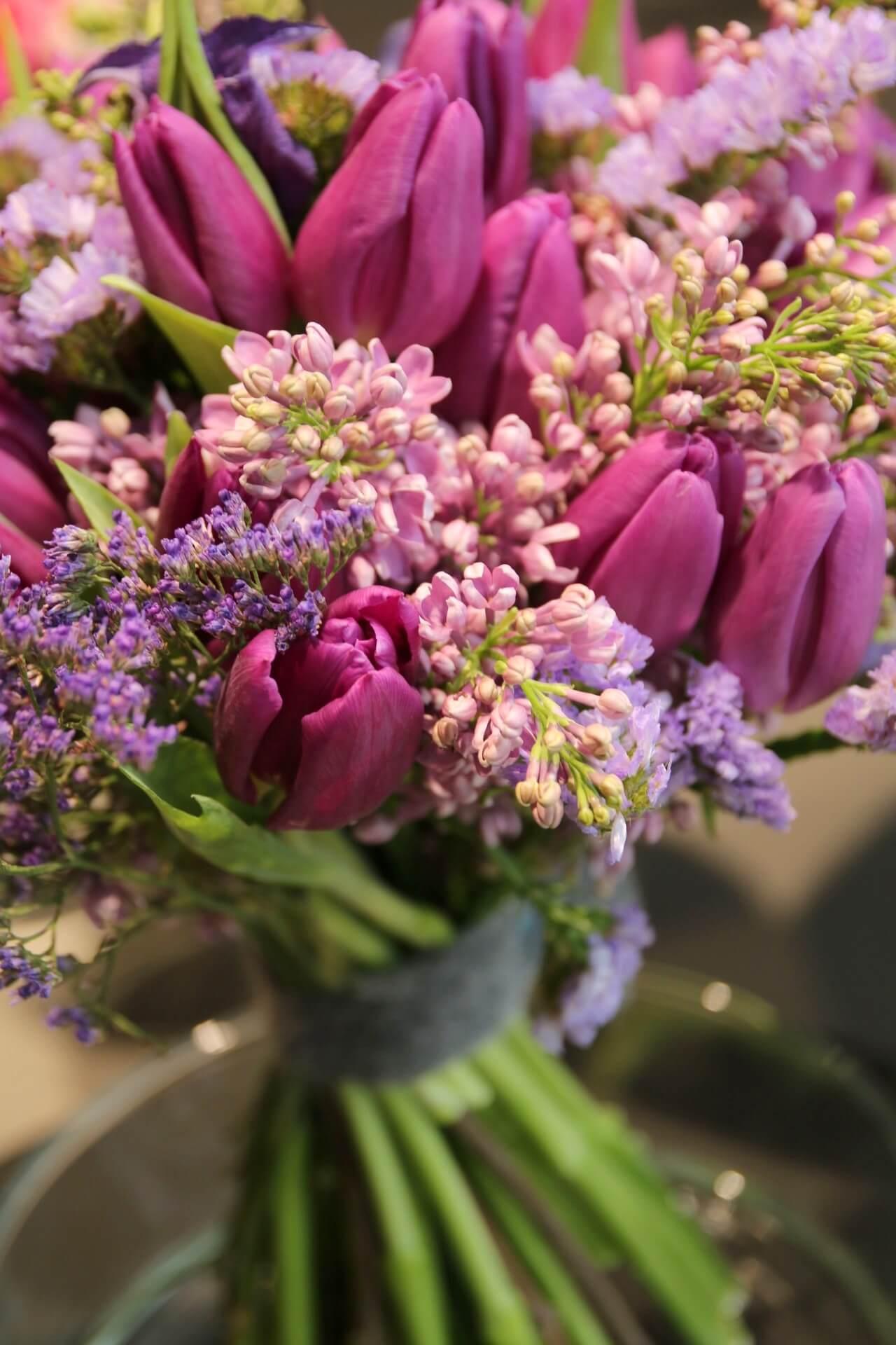 Lilat tulppaanit on sidottu tiiviiksi kimpuksi syreenien ja ikiviuhkon kanssa.