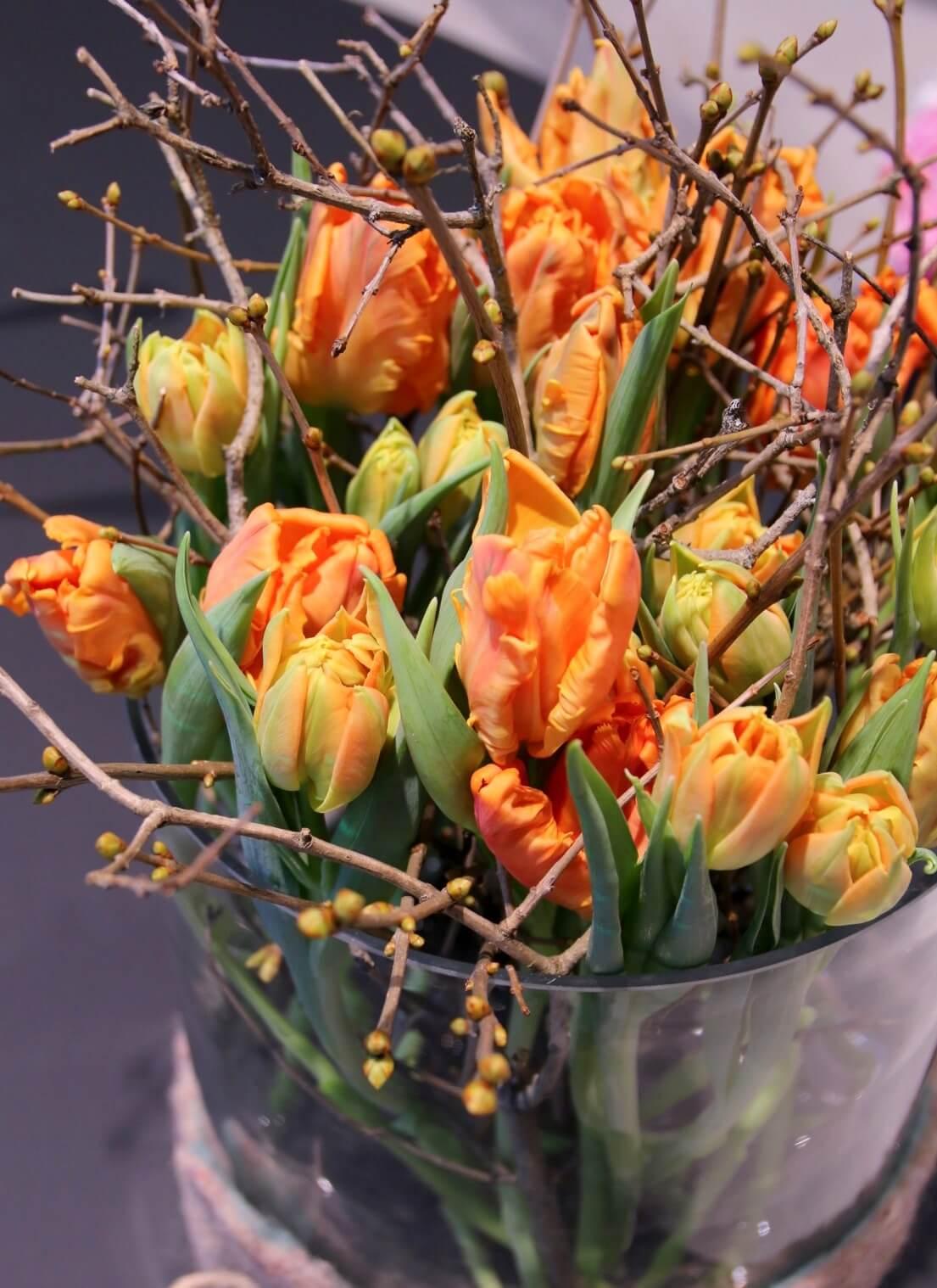 Lasiastia on täytetty oksilla ja oransseilla papukaija- sekä kerrotuilla tulppaaneilla.