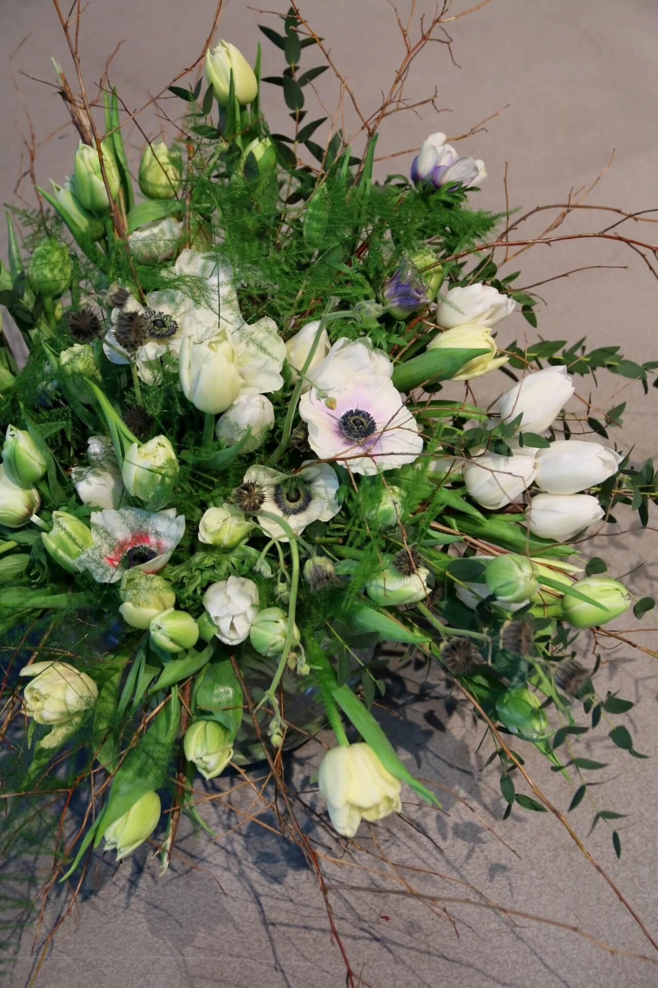 Valkoisista tulppaaneista ja oksista sidottuun isoon kimppuun on yhdistetty anemonea eli kruunuvuokkoa ja eukalyptusta.
