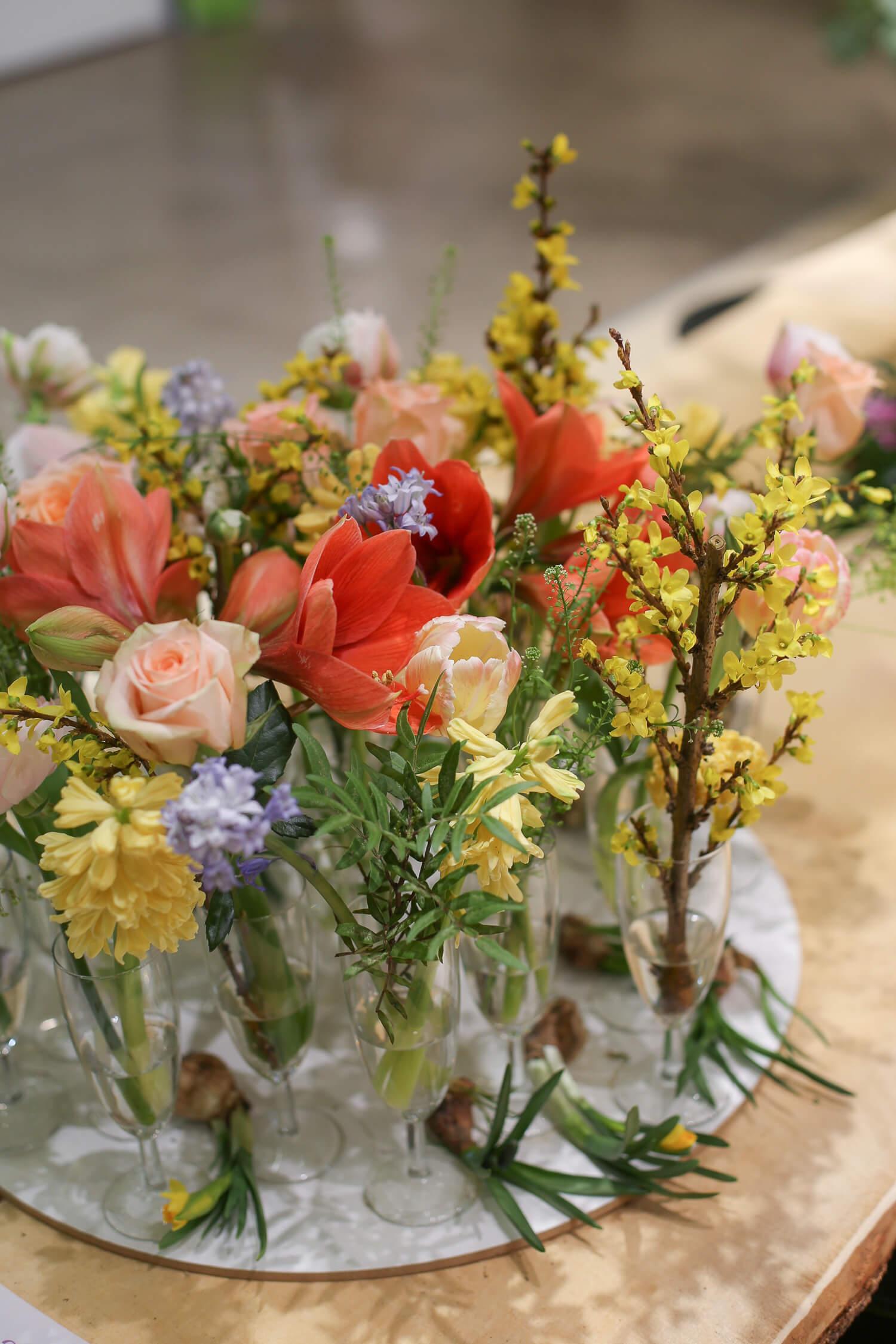 Helppo ja näyttävä asetelma syntyy puutarhajuhliin kun teet kukkaryhmän kuohuviinilaseista ja täytät ne kukkasilla.