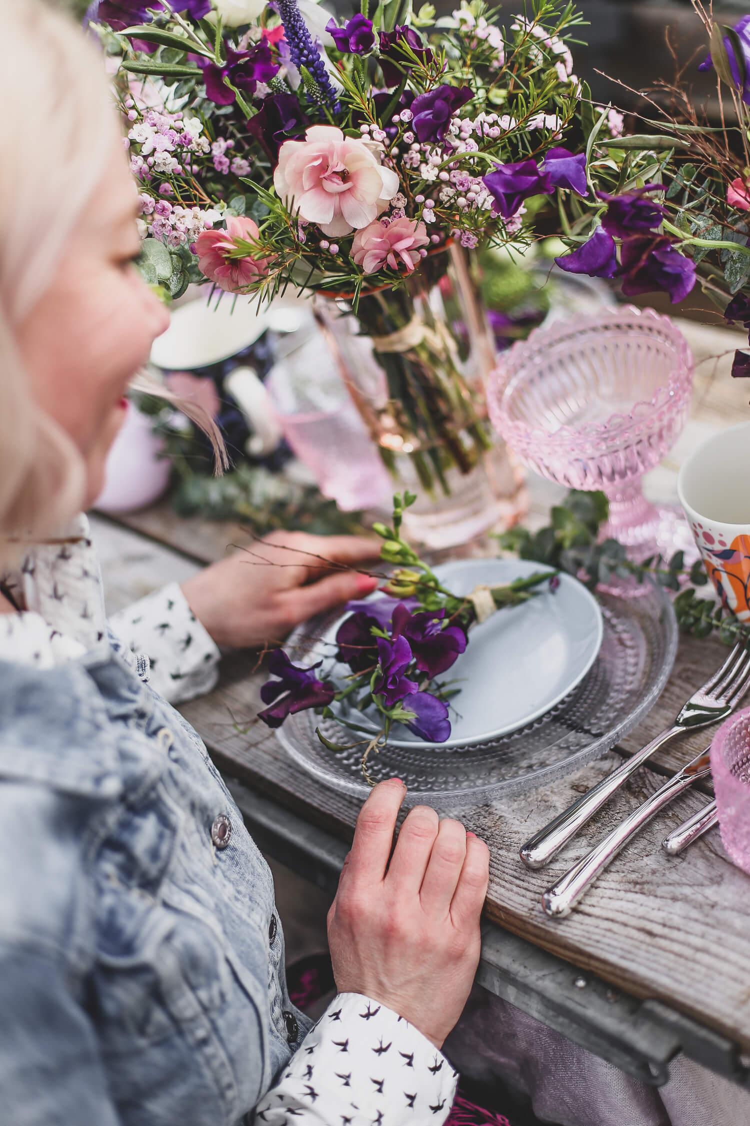 Kattaukseen lautasen päälle on sidottu minikimppu samoista kukista kuin pöydänk kimpuissa.
