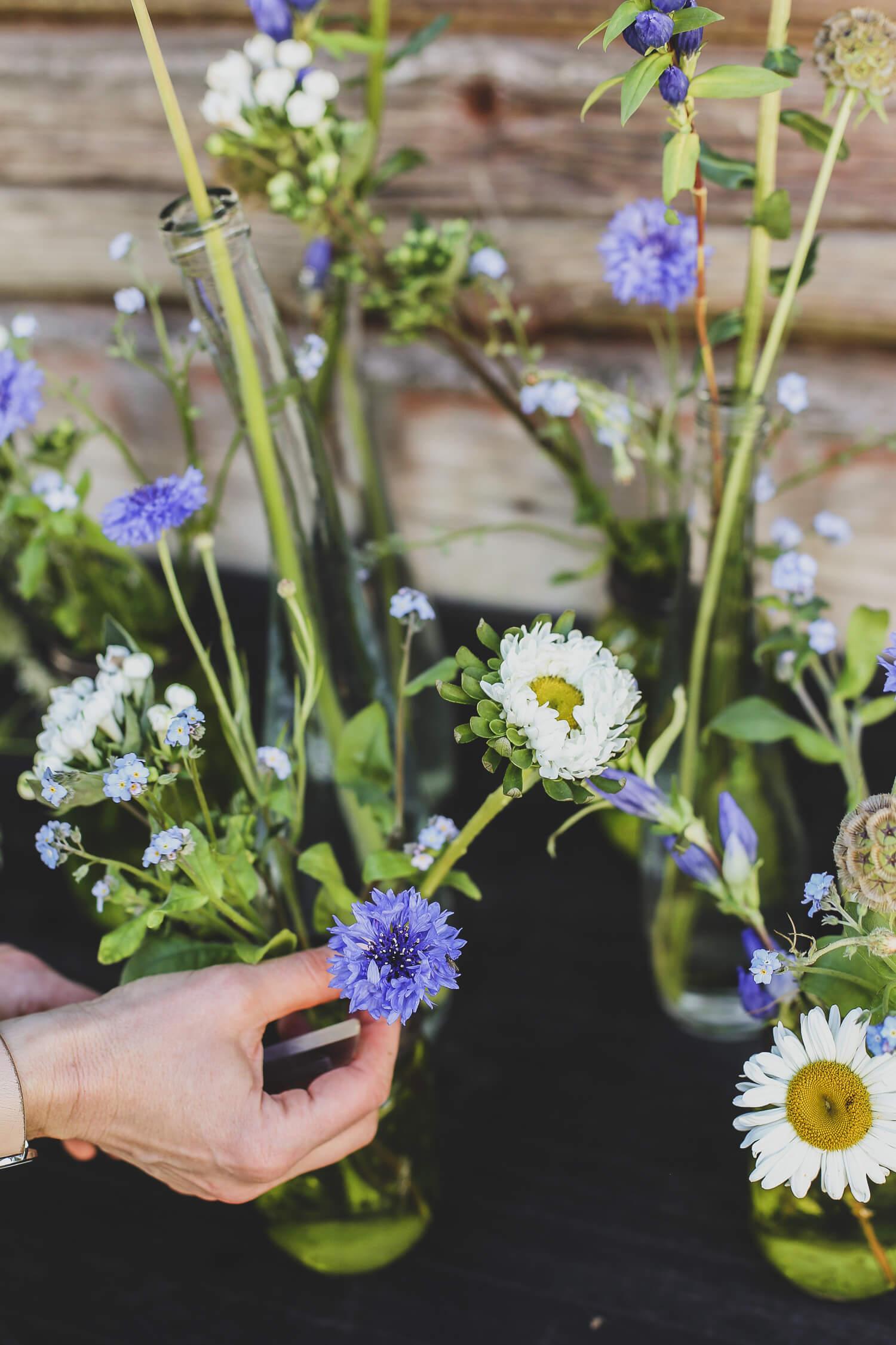 sinivalkoiset kukat lasipulloissa