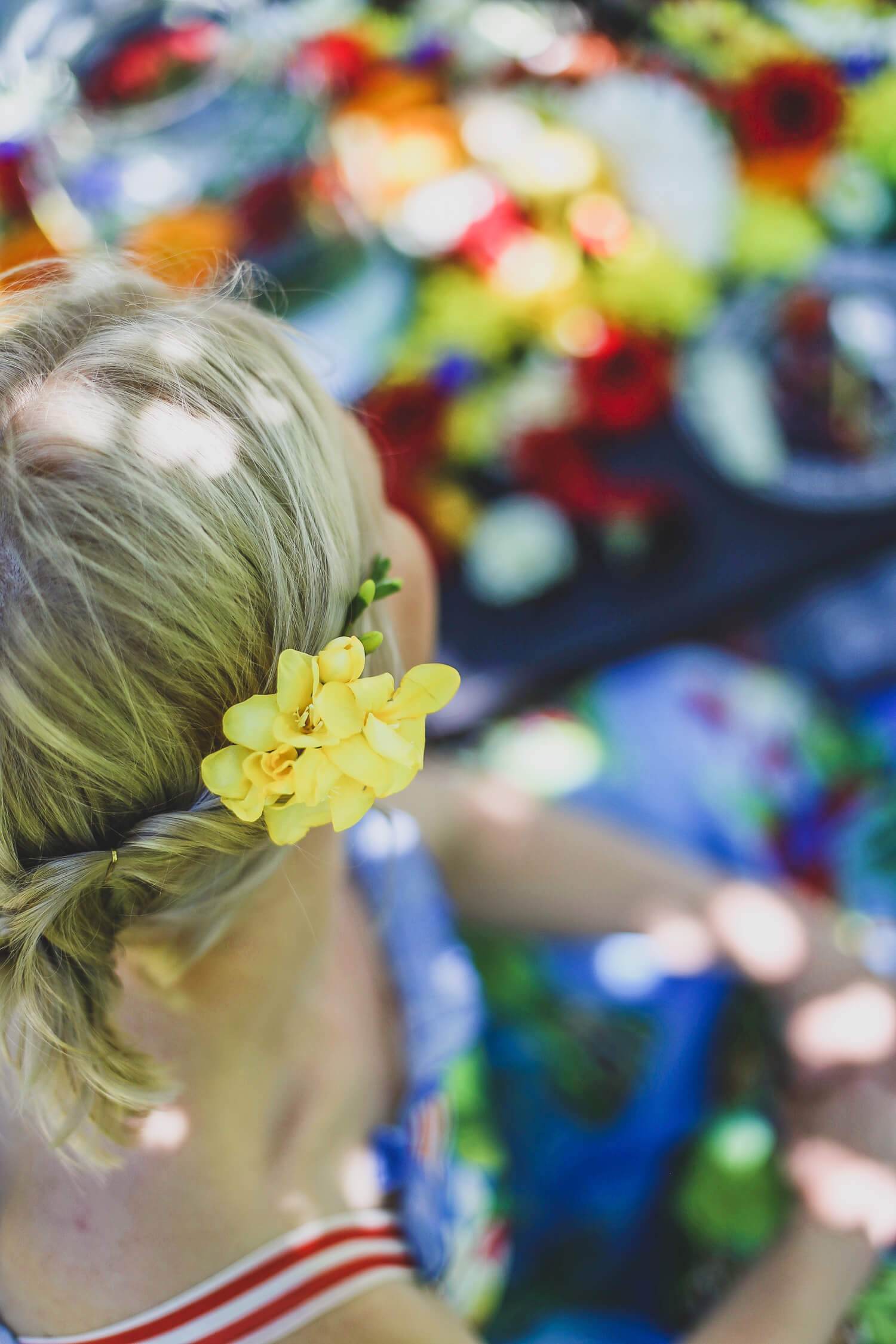 Kesäloman kukkapiknik on katettu ulos puutarhaan. Pöytäasetelmana toimii paljon erilaisia värikkäitä kukkia.