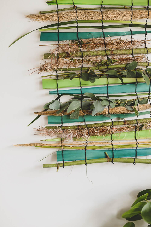 oksista ja kasveista on punottu kasviryijy työhuoneen seinälle koristamaan sitä.