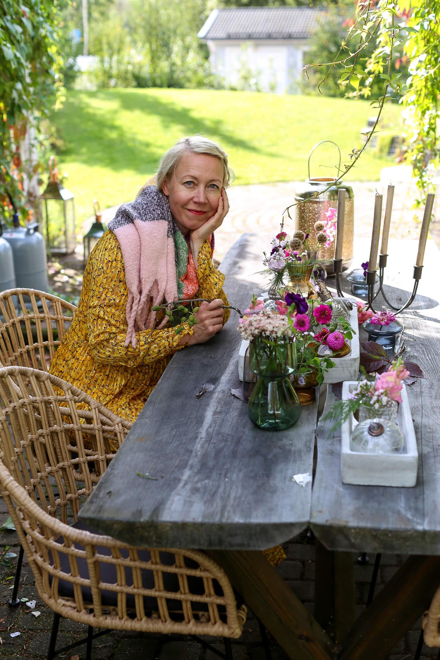 puutarhan pöydällä on kukkia ja kynttilöitä.