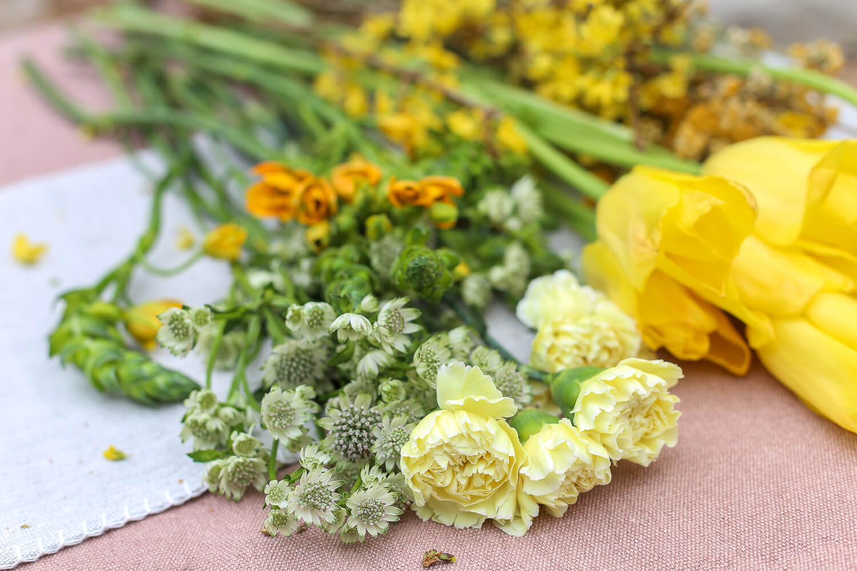 Kimpussa on käytetty keltaista neilikkaa, oranssitähdikkiä, ranskalaista tulppaani, onnenpensaan oksia ja tähtiputkea.