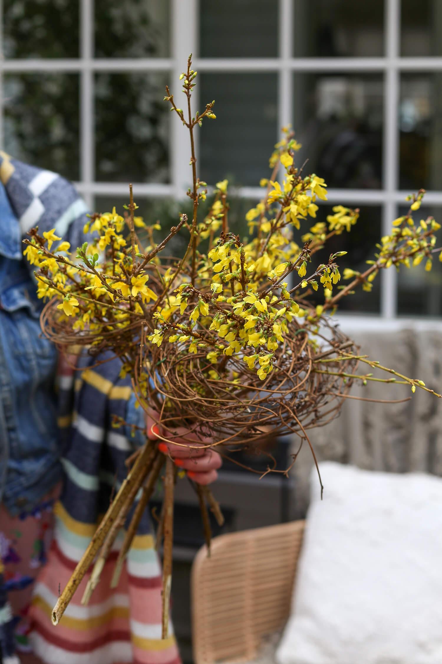 """Kukkakimpun pohjana on käytetty koriste""""pesistä"""" tehtyä risurakennetta."""