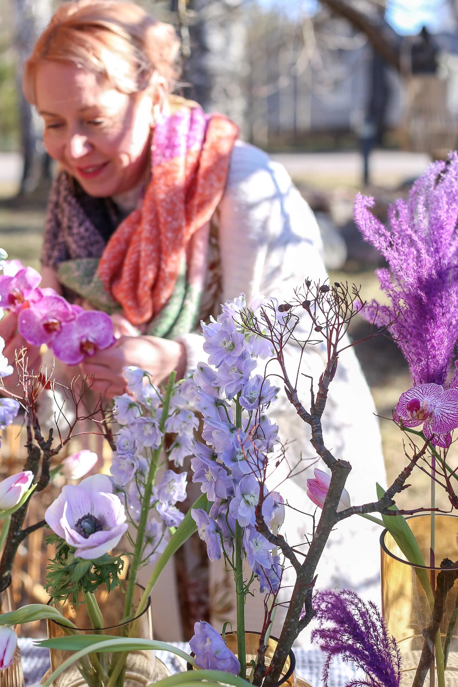 Puutarhapöydälle on tehty kukka-asetelma johon on koottu erilaisia ruskean sävyisiä maljakoita ja niissä on liloja kukkia.