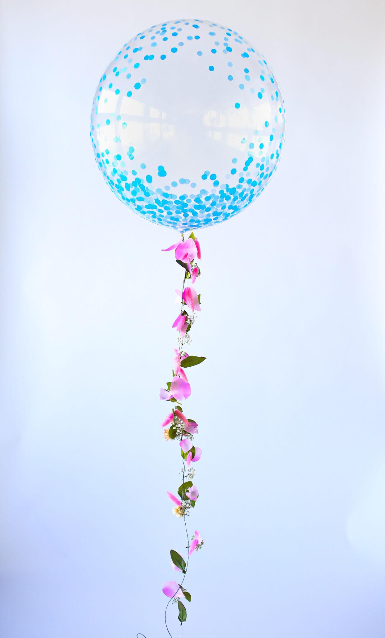 Ilmapallo koristeltiin kukan terälehdillä ja vihreillä versoilla.